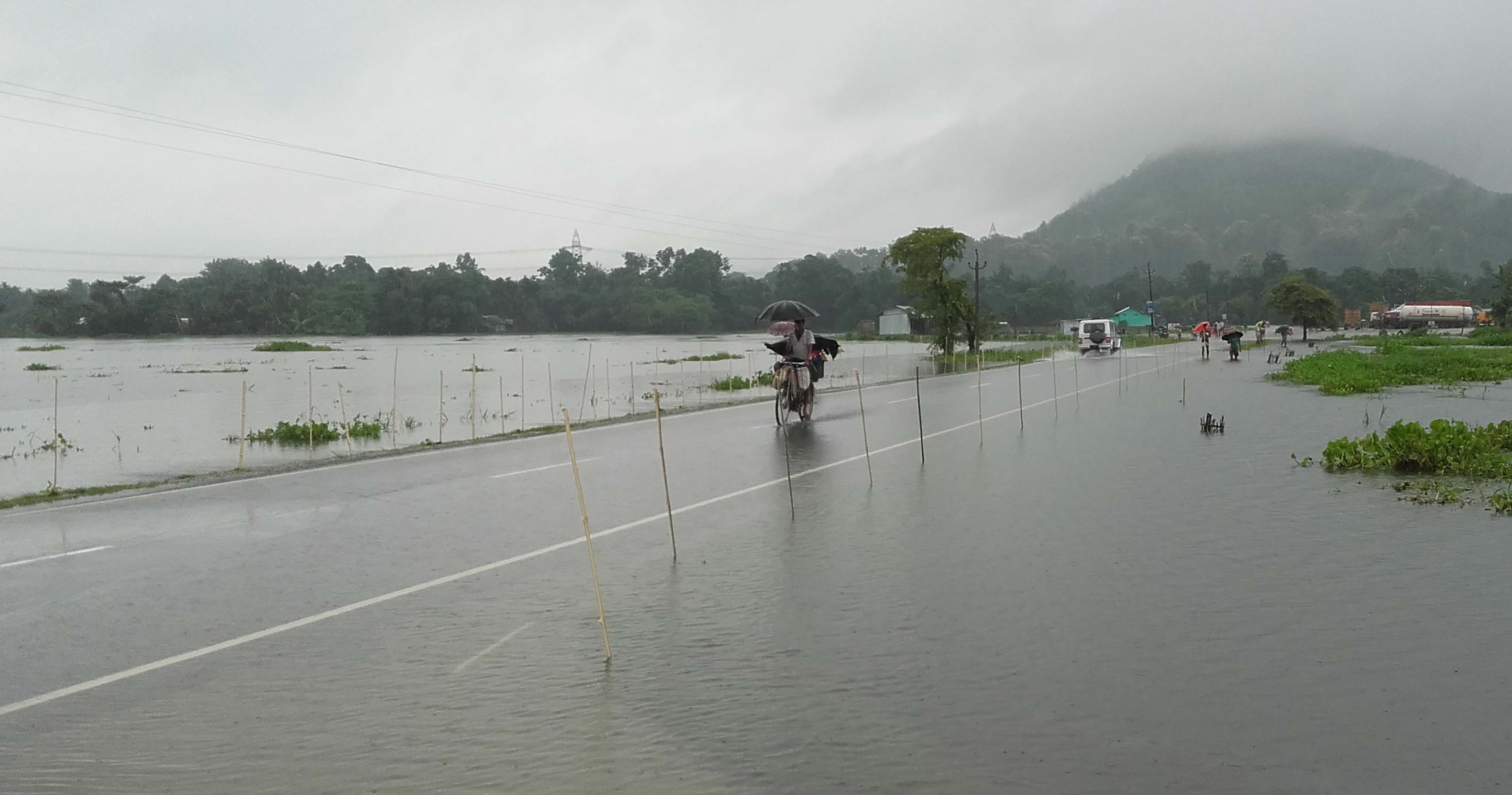 People passing in flooded NH 31 at Jharaguri jn Bongaigaon on Saturday. Photo by UB Photos.