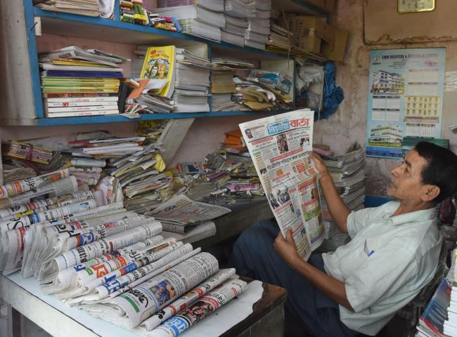 A newspaper salesman reads a local newspaper during Janata Curfew at Tezpur on 22-03-2020. Pix by UB Photos