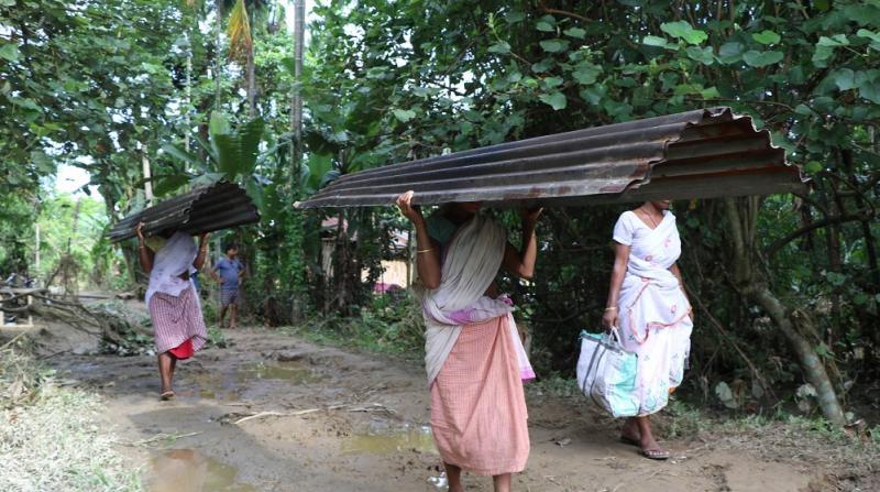 Fresh effort: Women heading home to build their ravaged homes afresh in Guri Jan Gohain Village, Gogamukh in Dhemaji District on Thursday. Photo by UB Photos