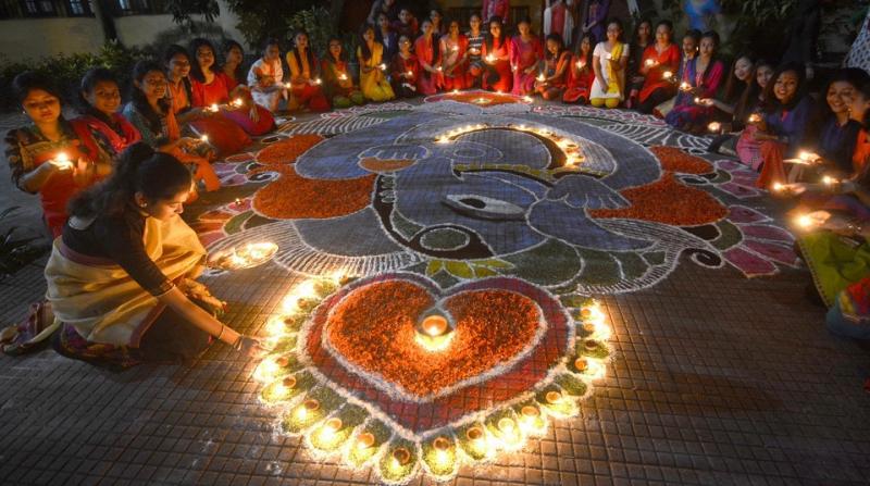 Students of Nalini Bala Devi Girls' Hostel, Cotton University lightning lamps on Thursday. Pix by UB Photos.