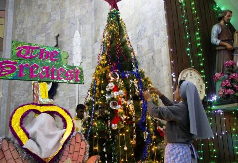 A Nun giving final touch to a Christmas tree at Don Bosco Catholic Church, Guwahati