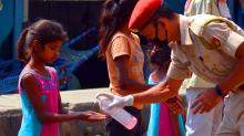 A policeman giving hand sanitizer to a young girl at road side in Guwahati