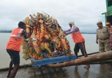 GMC worker carrying an idol of Goddess Durga for immersion in the Brahmaputra river on Bijoya Dashami at Kasomari Ghat in Guwahati on Saturday. Photo by UB Photos